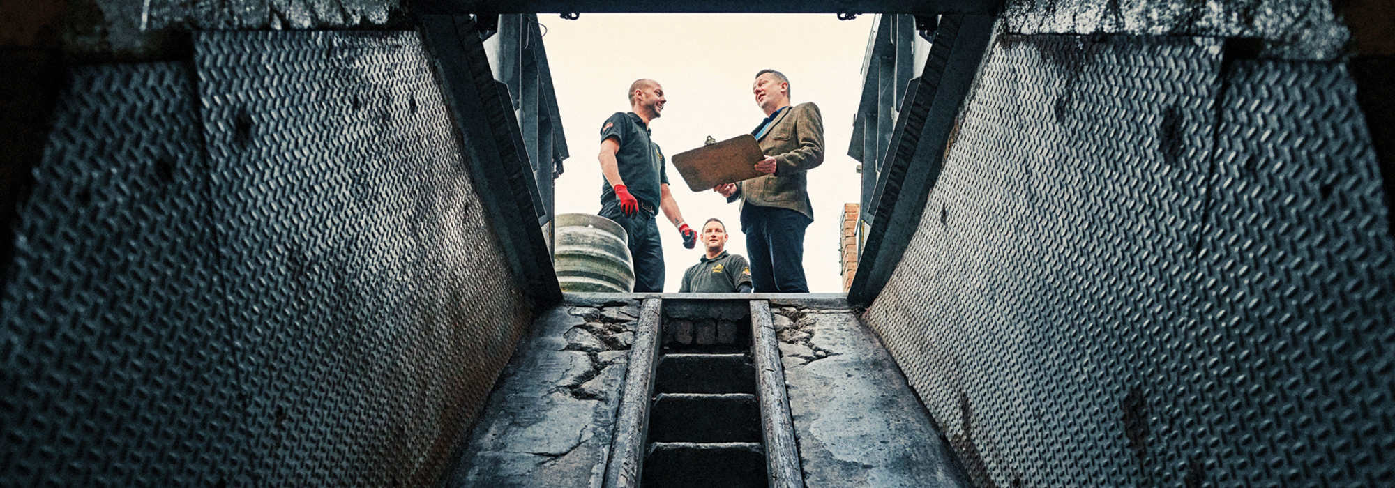 View from a pub cellar with a delivery man at the top of the stairs