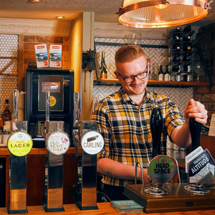 Man behind a bar pulling a pint