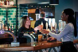 Bar tender handing drink to cutomer