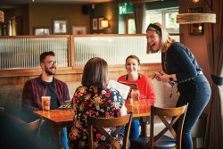 Waitress taking order from a table of customers in a pub