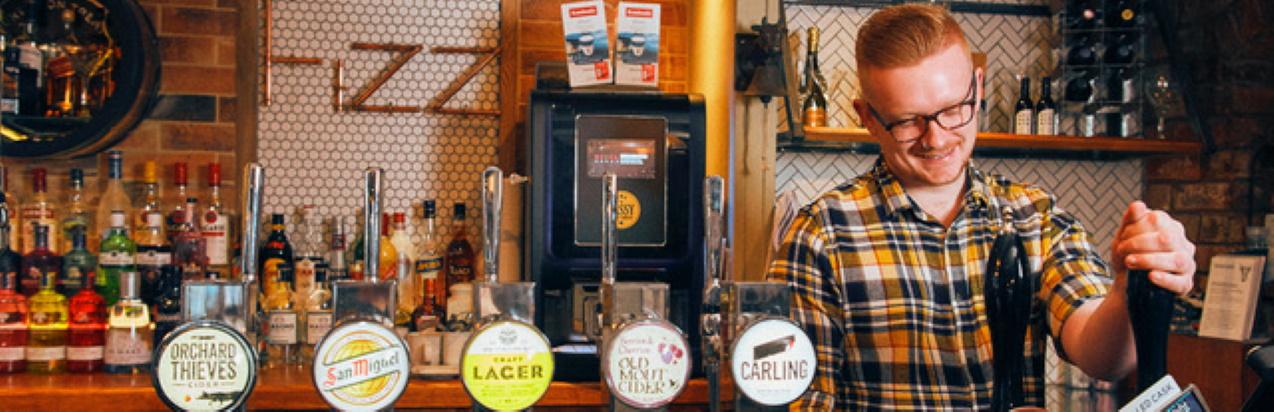 Man behind a bar pulling a pint of beer