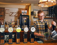 Man behind a bar pulling a pint of beer