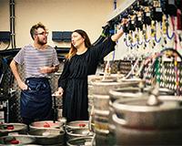 Man and woman in pub cellar check barrel lines