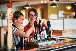 Two women behind a bar